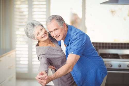 Portrait of cheerful senior couple dancing in kitchen at home