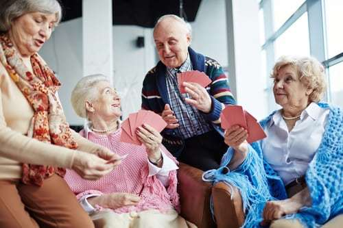 Group of friendly seniors playing cards at leisure