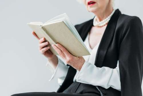 A senior woman reading a book wearing a blazer and pearls.