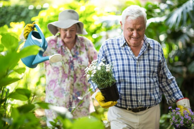 Senior couple carrying water can surrounded by plants