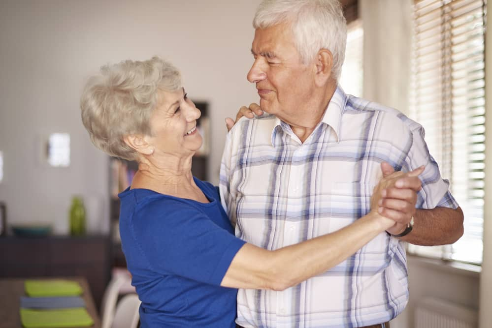 Senior-couple-dancing-happily-at-home