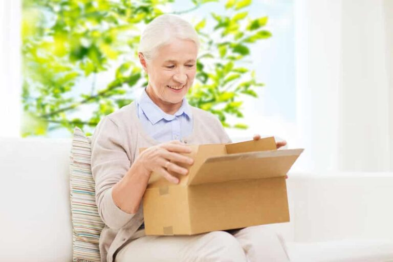 Smiling-senior-woman-opening-cardboard-package-at-home