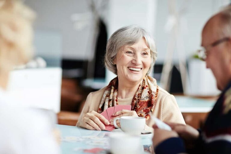 senior woman smiling while playing cards with friends