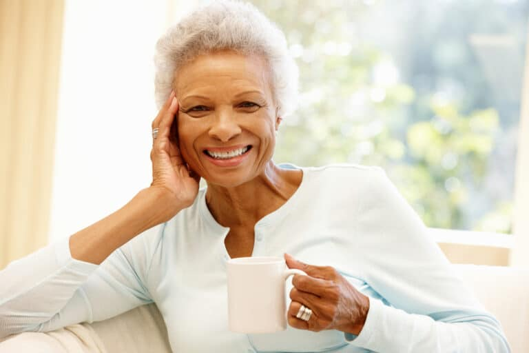 Senior woman smiling and holding mug while sitting on couch