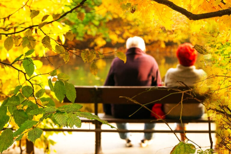 Senior couple sitting on bench in fall