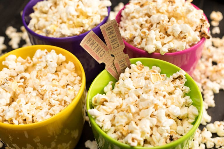 Four bowls filled with popcorn, cinema tickets